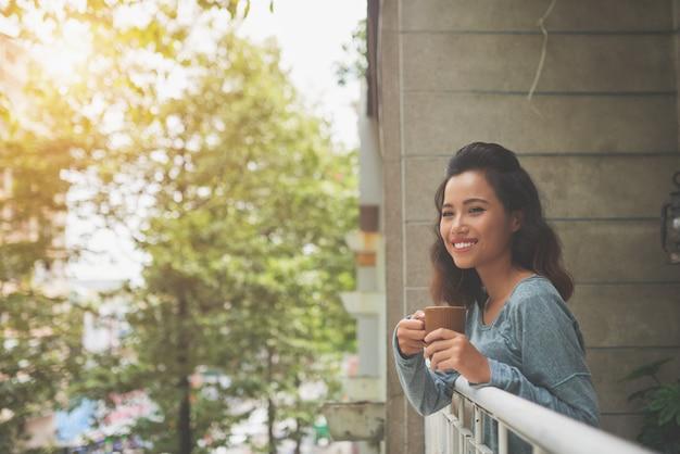 Señora atractiva joven sonriendo a la cámara de pie en el balcón y relajarse con una taza de té Foto gratis