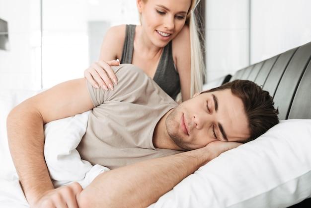 Señora bonita sonriente que despierta a su marido durmiente en la cama Foto gratis