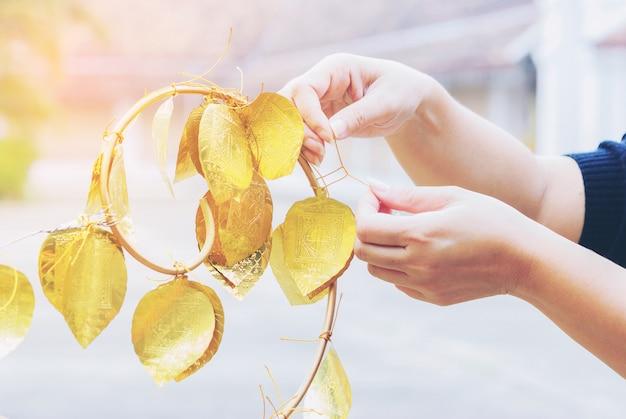 Una señora está colgando la hoja dorada de los deseos de felicidad en wat phrathat chae haeng. Foto gratis