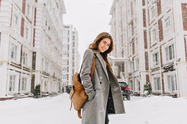 Señora elegante con mochila marrón caminando por la ciudad bajo la nieve. foto al aire libre de una mujer bonita con una sonrisa encantadora posando en abrigo gris en la escena urbana Foto gratis