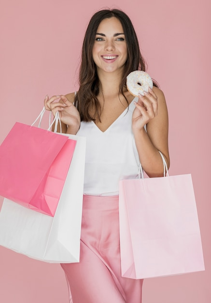 Señora feliz con bolsas de compras y una rosquilla Foto gratis