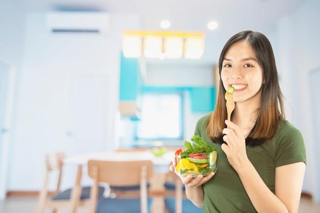 Señora feliz que sostiene cosas de la cocina sobre fondo del espacio de la copia Foto gratis