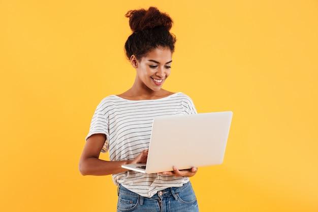 Señora fresca positiva joven con el pelo rizado usando laptop aislado Foto gratis