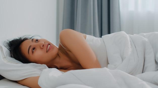 La señora india asiática duerme en sitio en casa. joven asiática se siente feliz relajarse descansar acostado en la cama, sentirse cómodo y tranquilo en el dormitorio en la casa por la mañana. Foto gratis