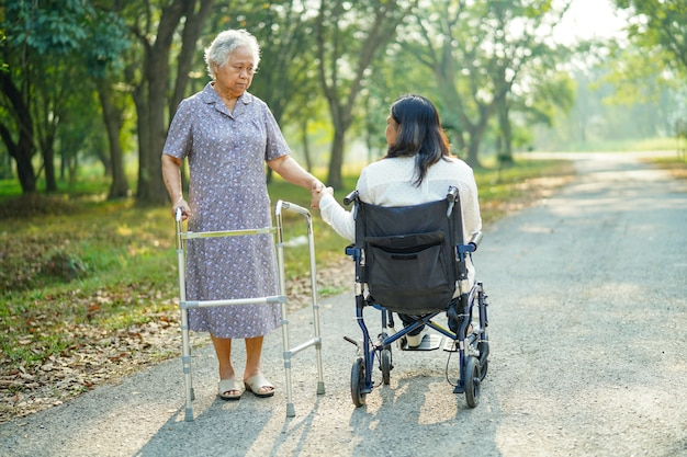 Señora mayor asiática caminar con andador y mujer en silla de ruedas en el parque. Foto Premium