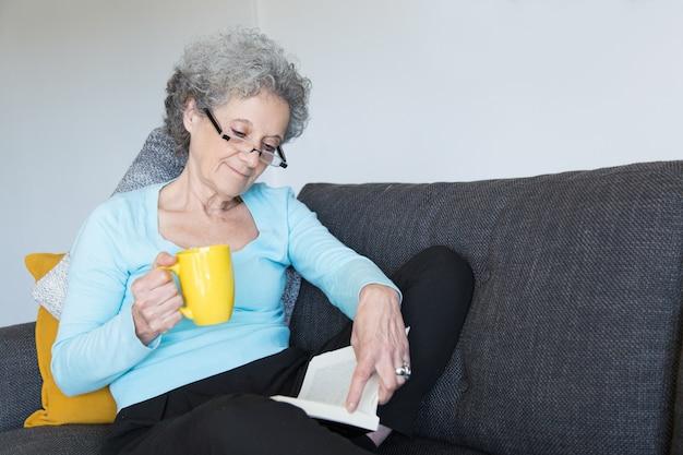 Señora mayor positiva que disfruta de la novela emocionante Foto gratis