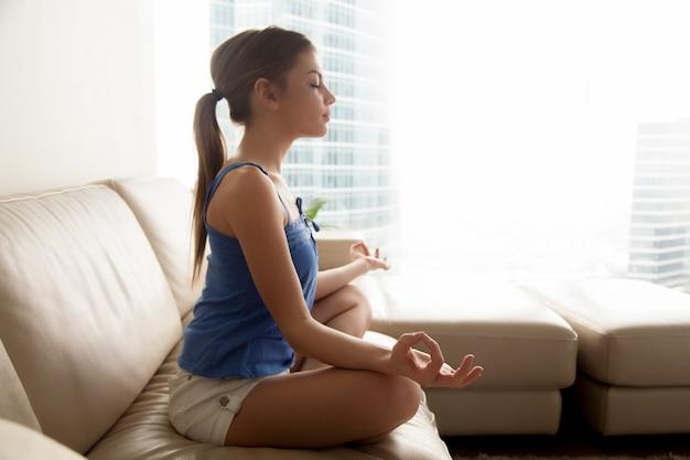 Señora practicando yoga y relajandose en casa Foto gratis