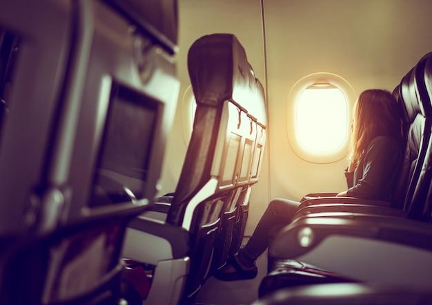 La señora está sentada en el avión mirando el sol brillante a través de la ventana Foto gratis