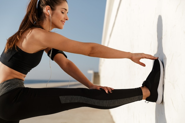 Señora sonriente haciendo ejercicios mientras entrena Foto gratis