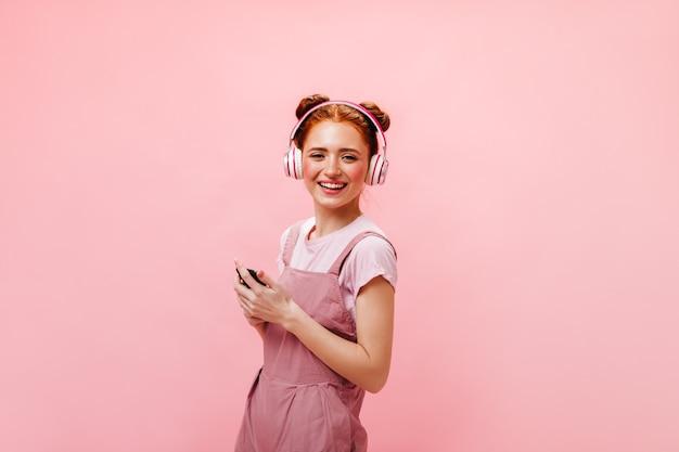 Señorita con bollos mira la pantalla del teléfono con sorpresa. mujer vestida y camiseta blanca está escuchando música con auriculares sobre fondo rosa. Foto gratis