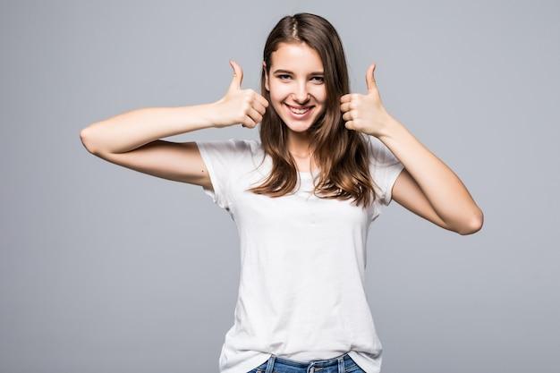 Señorita en camiseta blanca y jeans azul muestra los pulgares para arriba cantan frente a fondo blanco de estudio Foto gratis
