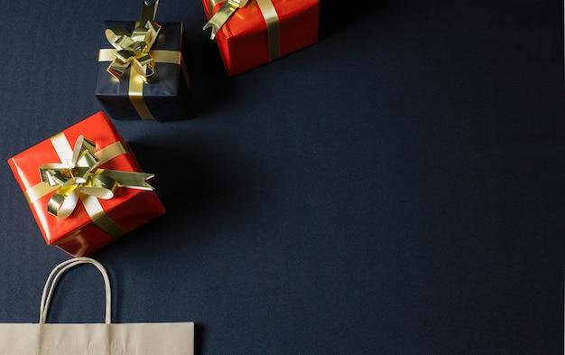 Sentar planas de una bolsa de papel ecológico marrón y cajas de regalo de navidad con espacio de copia Foto gratis