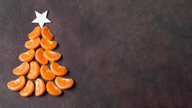 Sentar planas de forma de árbol de navidad de mandarinas con espacio de copia Foto gratis