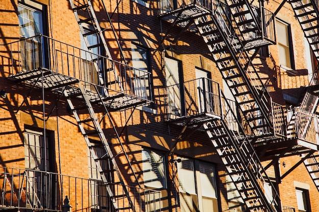 Serie de escaleras de escape en caso de incendio en la fachada de un edificio de apartamentos de ladrillo en la ciudad Foto gratis