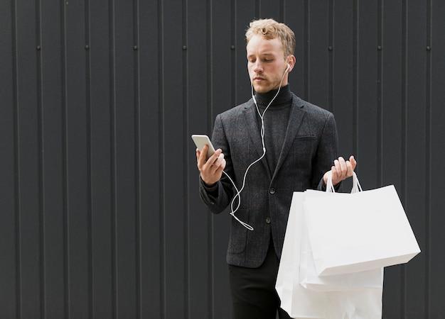En serio hombre de negro con auriculares y teléfono inteligente Foto gratis