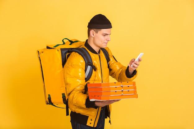 Servicio de entrega sin contacto durante la cuarentena. el hombre entrega comida y bolsas de compras durante el aislamiento. emociones del repartidor aislado en amarillo Foto gratis