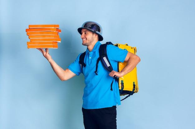 Servicio de entrega sin contacto durante la cuarentena. el hombre entrega comida y bolsas de compras durante el aislamiento. emociones del repartidor aislado en azul Foto gratis