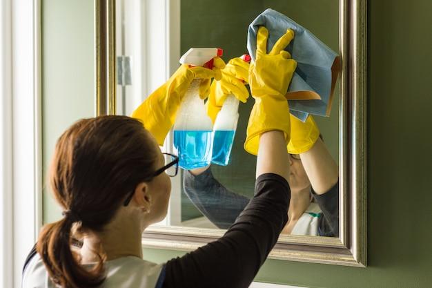 Servicio de limpieza, mujer limpia espejo en baño en casa Foto Premium