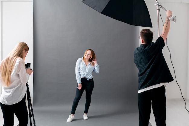Sesión fotográfica con modelo femenina y fotógrafos. Foto gratis