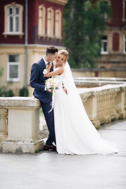 Sesión de fotos de boda. novia y el novio caminando en la ciudad. pareja casada abrazándose y mirándose. sosteniendo el ramo. exterior, cuerpo completo Foto Premium