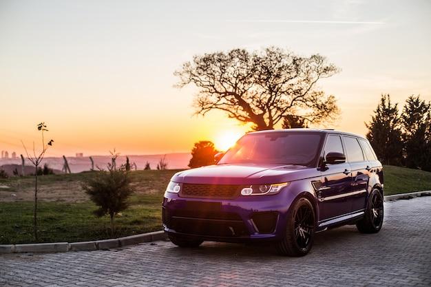 Una sesión de fotos de jeep azul en la puesta de sol. Foto gratis