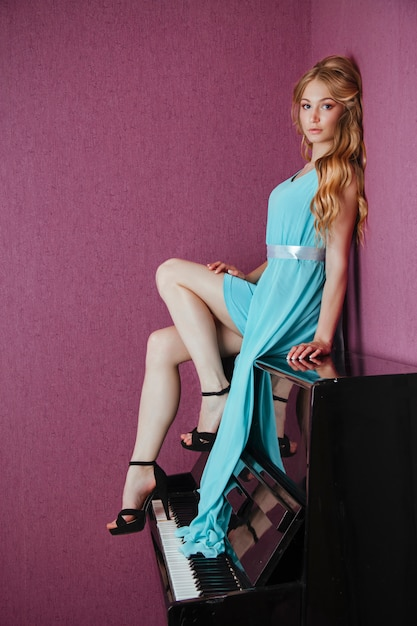 Sexy hermosa chica rubia en vestido tocando el piano Foto Premium
