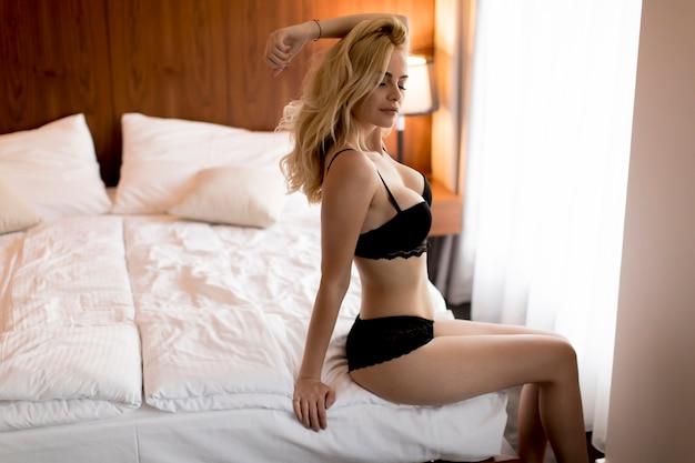455953c744 Sexy mujer rubia en ropa interior sentada en la cama Foto Premium