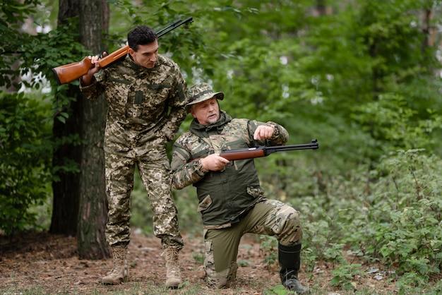 Shooter recarga escopeta papá e hijo cazando. Foto Premium
