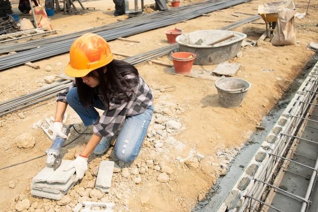 Sierra redonda en manos del constructor, trabajo en colocación de losas. Foto gratis