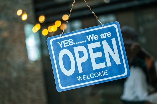 Signo abierto a través del cristal de la ventana en la cafetería Foto gratis