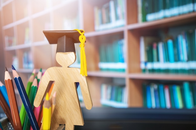Signo de la gente de madera graduación celebración tapa con lápices de colores en la universidad de la biblioteca