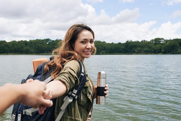 Un sígueme disparó con una chica asiática tirando de la mano de su novio anónimo y sonriendo Foto gratis
