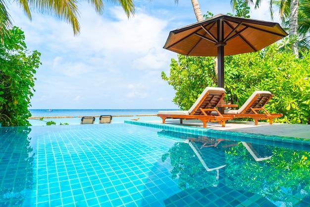 Silla de playa con piscina y vistas al mar en maldivas Foto Premium