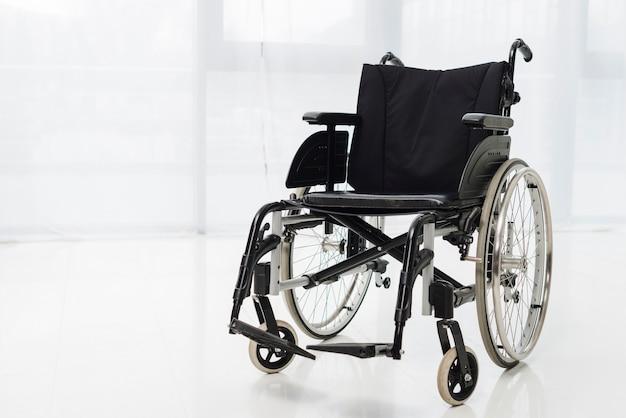 Silla de ruedas moderna vacía en habitación Foto gratis