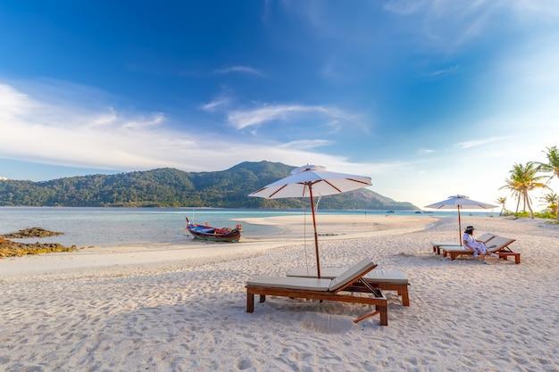 Sillas de playa, sombrillas y palmeras en la hermosa playa para vacaciones y relajación en la isla de koh lipe, tailandia Foto Premium