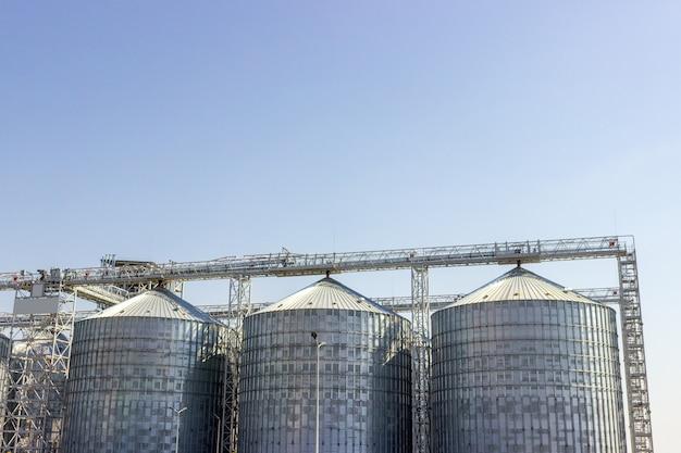 Silos de cereales bajo el cielo azul. almacenaje industrial. Foto Premium