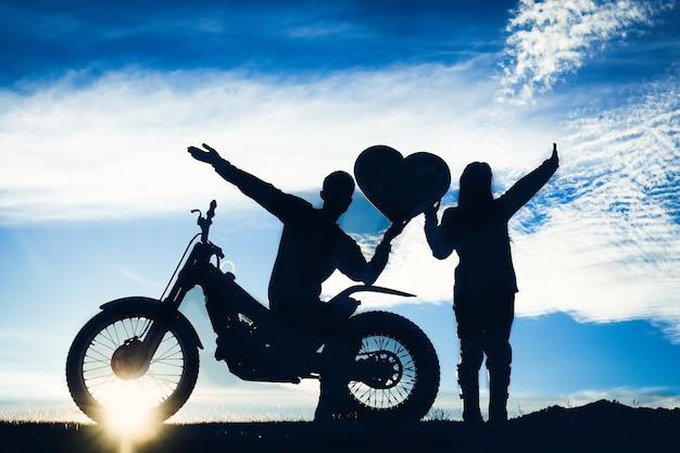 Silueta De Amantes Románticos Y Motocross Con Puesta De Sol