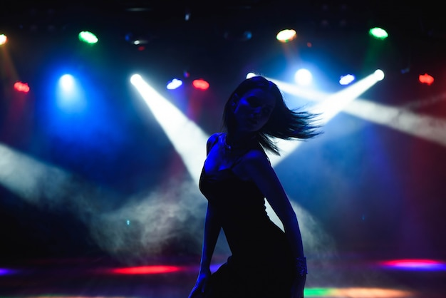 Silueta de bailarina contra luces de discoteca Foto Premium