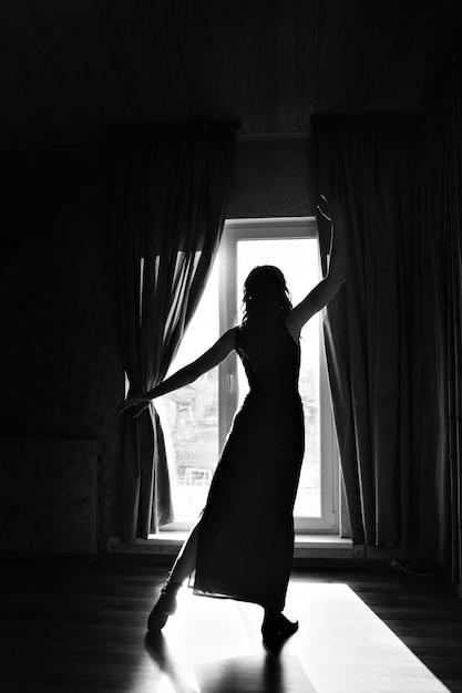 Silueta de una bailarina en la ventana. una mujer a la luz. el concepto de fortalecer el cuerpo femenino, la gracia, el deporte, la belleza, el estilo. Foto Premium