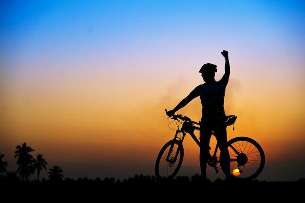 Silueta del ciclista con bicicleta de montaña en la hermosa puesta de sol. Foto Premium