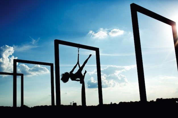 Silueta de danza aérea de seda en la azotea al atardecer Foto gratis