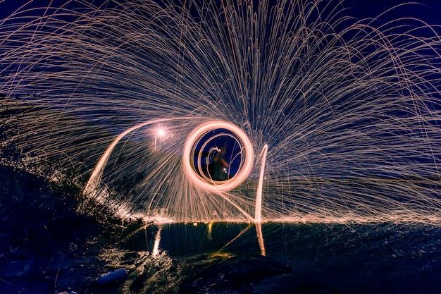 Silueta de hombre haciendo un círculo de chispas por la noche Foto Gratis