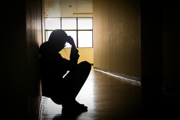 Silueta de empresaria sentado cabeza en manos de la oficina creativa moderna. concepto dramático de soledad, tristeza, depresión, emociones tristes, llanto, desilusión. Foto Premium