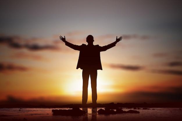 Silueta del empresario levantó las manos y rezando a dios Foto Premium