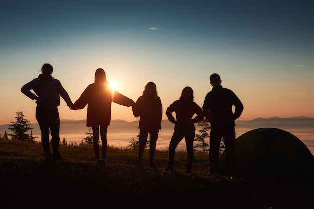Una silueta de grupo de personas se divierte en la cima de la montaña cerca de la carpa durante la puesta de sol. Foto gratis