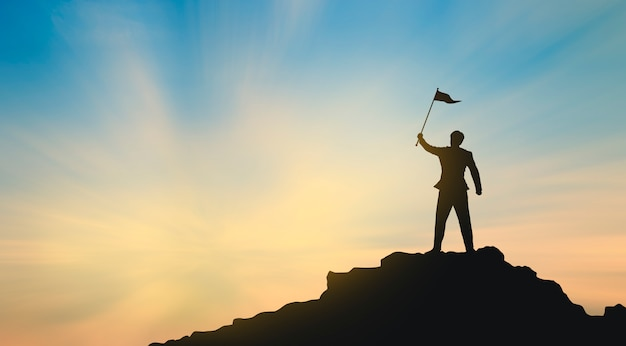 Silueta del hombre en la cima de la montaña sobre el cielo y la luz del sol, el éxito del negocio, el liderazgo, el logro y el concepto de la gente Foto Premium