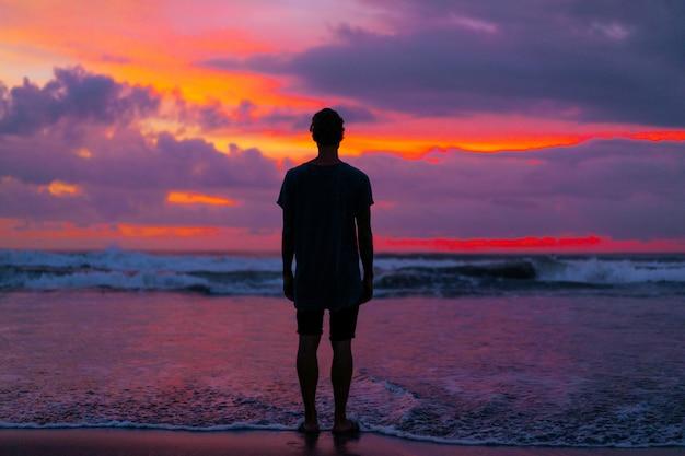 Silueta de un hombre en el contexto de una hermosa puesta de sol de color brillante en el océano Foto Premium