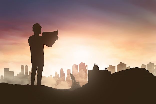 Silueta de hombre ingeniero mirando su plano en construcción Foto Premium