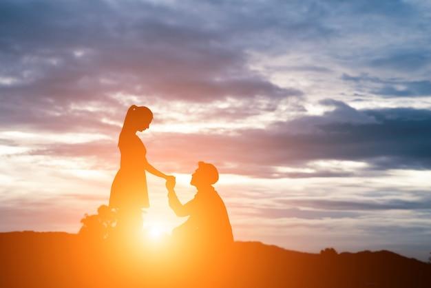 Silueta del hombre pida mujer para casarse en el fondo de la montaña. Foto gratis