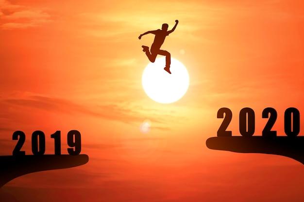 Silueta del joven empresario saltando de 2019 a 2020 Foto Premium